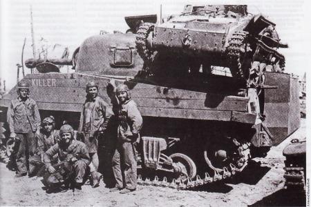 "Namur, Marshall Islands, Maret 1944, Sebuah tank M4A2 Sherman ""Killer"" dari C Company, Marine 4th Battalion. Para awak tank Marinir sengaja mengangkut tank ringan Jepang Type 94 di atas dek mesinnya. Perhatikan fasilitas lapisan papan kayu di sekujur tubuh tank. Lapisan ini dipakai untuk menangkal serangan ranjau antitank jenis magnet Type 99 milik Jepang. Fasilitas lain yang cukup unik bisa dipergoki pada kotak berisi peralatan anti air yang menempel di belakang tank Sherman"